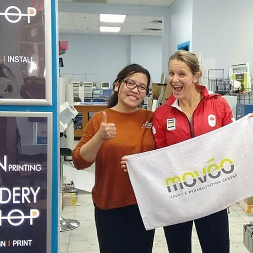 "One if instant Imprints New West's owners and a customer holding a white custom sign for her business. Her sign says ""Moveo"""