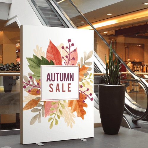 "A large, custom foam core sign in a mall. It's standing right in front of the escalator and reads ""autumn sale"" on the front."
